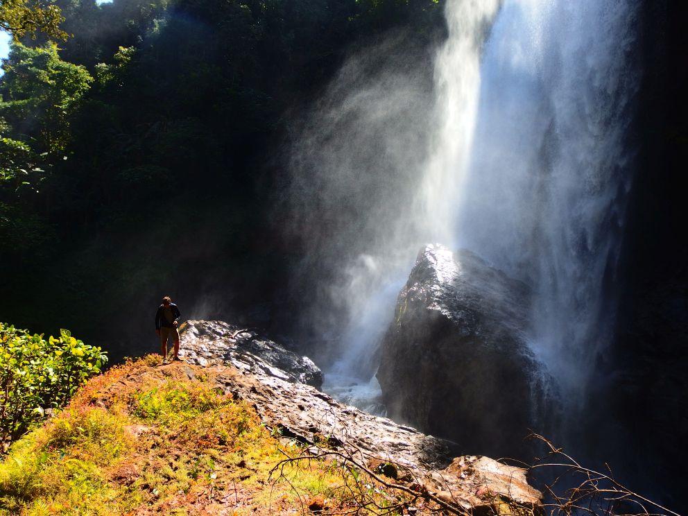 Epicki wodospad i mały, szary człowieczek